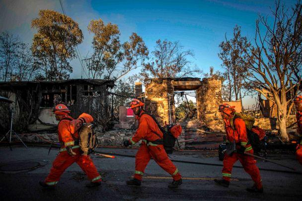 PHOTO: Firefighters walk past a burnt home during the Getty Fire in Brentwood, Calif., Oct. 28, 2019. (Apu Gomes/AFP/Getty Images)