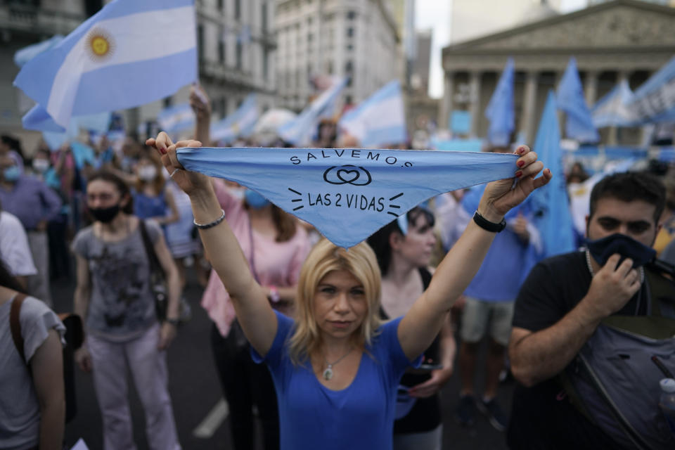 """An activist against abortion holds a handkerchief with text in Spanish that reads """" Save both lives,"""" as she protests against the decriminalization of abortion, one day before lawmakers will debate its legalization, at Plaza de Mayo in Buenos Aires, Argentina, Monday, Dec. 28, 2020. (AP Photo/Victor R. Caivano)"""