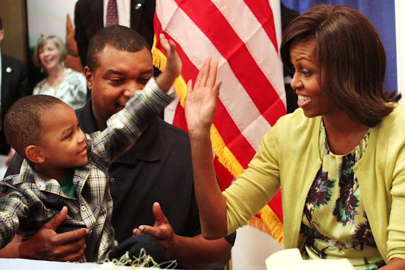 First lady Michelle Obama gets a high five with Eun White, seated with his father, Army Maj. Eunotchol White, during the first lady's visit to Fisher House at Walter Reed National Military Medical Center in Bethesda, Md., Wednesday, April 4, 2012. The Fisher House program houses military families while a family member is receiving medical care. (AP Photo/Jacquelyn Martin)