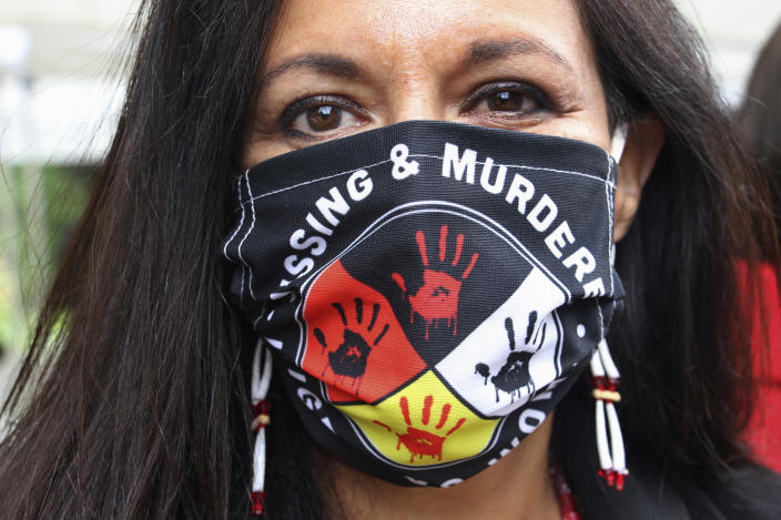 FILE - In this Wednesday, Aug. 26, 2020, file photo, Jeannie Hovland, the deputy assistant secretary for Native American Affairs for the U.S. Department of Health and Human Services, poses with a Missing and Murdered Indigenous Women mask, in Anchorage, Alaska, while attending the opening of a Lady Justice Task Force cold case office in Anchorage, which will investigate missing and murdered Indigenous women. From the nation's capitol to Indigenous communities across the American Southwest, top government officials, family members and advocates are gathering Wednesday, May 5, 2021, as part of a call to action to address the ongoing problem of violence against Indigenous women and children. (AP Photo/Mark Thiessen, File)