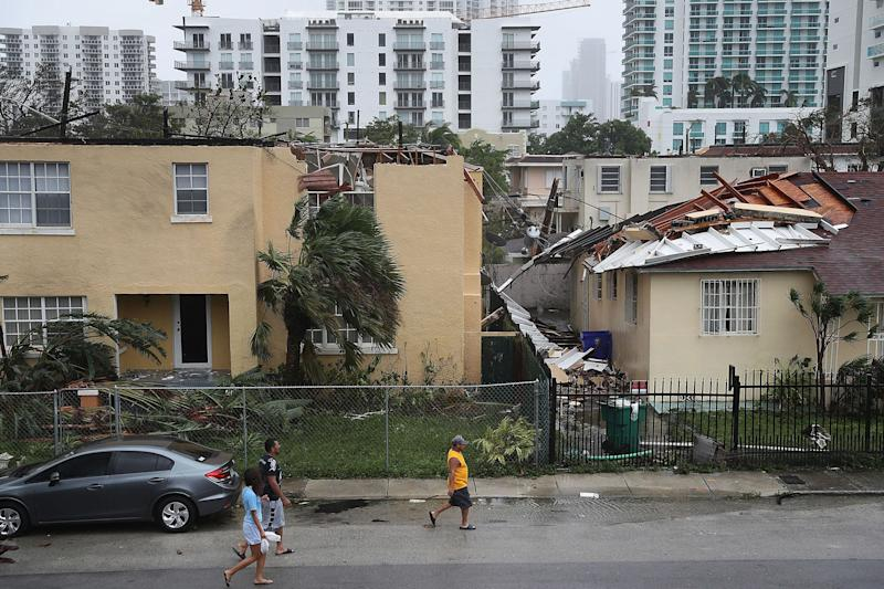 MIAMI, FL - SEPTEMBER 10: People walk past a building where the roof was blown off by Hurricane Irma on September 10, 2017 in Miami, Florida. Hurricane Irma, which first made landfall in the Florida Keys as a Category 4 storm on Sunday, has weakened to a Category 2 as it moves up the coast. (Photo by Joe Raedle/Getty Images)