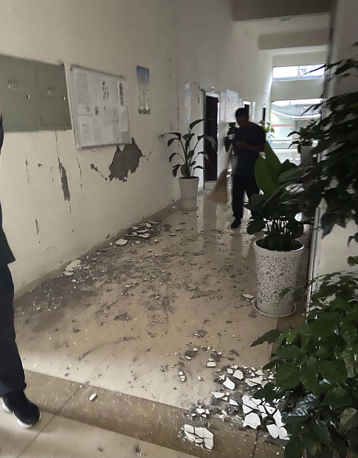 In this photo provided by Qiu Xin, people sweep up debris in the hallway of an office building after an earthquake in Luzhou in southwestern China's Sichuan Province, Thursday, Sept. 16, 2021. Rescue work was underway following a magnitude-6.0 earthquake early Thursday in southwest China's Sichuan province. (Qiu Xin via AP)