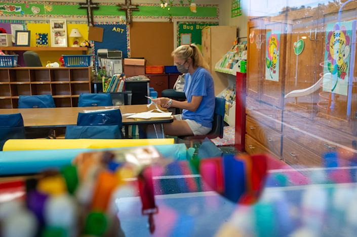 Liz Guidry working alone in her classroom preparing for when students return to school at Our Lady of Fatima Catholic School in New Orleans, Tuesday, July 28, 2020.