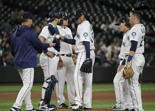 Seattle Mariners starting pitcher Felix Hernandez, center, is pulled from the baseball game against the Texas Rangers by manager Scott Servais, left, during the sixth inning Tuesday, May 29, 2018, in Seattle. (AP Photo/Ted S. Warren)