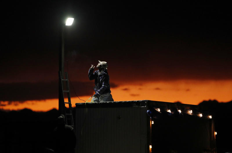 """A man sets up a a light in preparation for an event inspired by the """"Storm Area 51"""" internet hoax near the Little A'Le'Inn motel and cafe, Thursday, Sept. 19, 2019, in Rachel, Nev. Hundreds have arrived in the desert after a Facebook post inviting people to """"see them aliens"""" got widespread attention and gave rise to festivals this week. (AP Photo/John Locher)"""