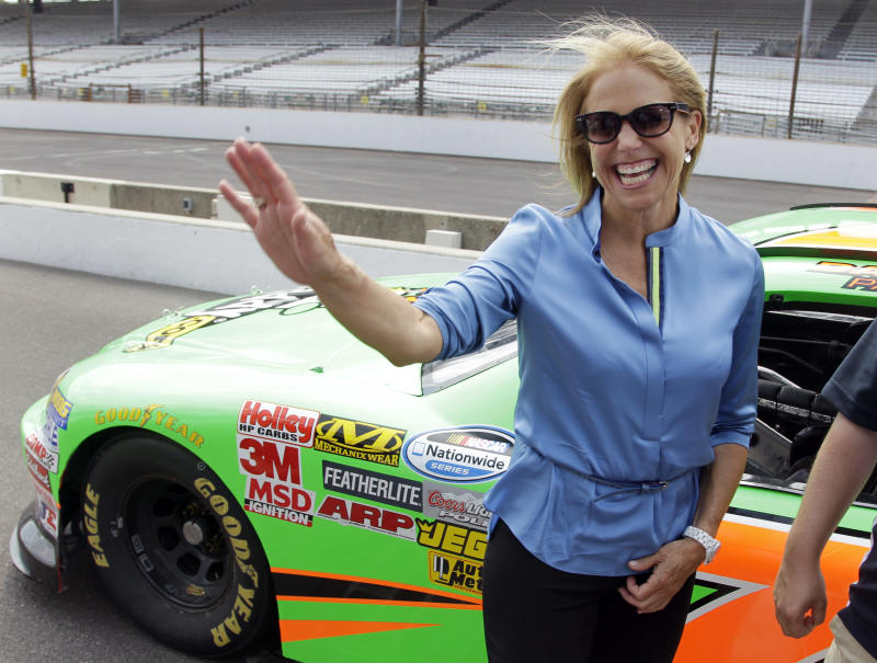 Journalist and television personality Katie Couric waves as she walks away from a car that she rode laps with race car driver Danica Patrick at the Indianapolis Motor Speedway in Indianapolis, Tuesday, July 10, 2012. (AP Photo/Michael Conroy)