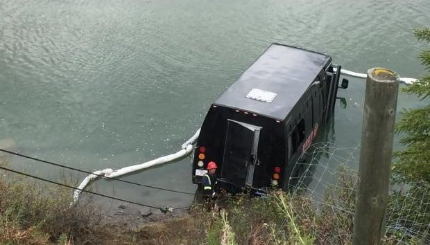 The bus that killed one woman and seriously injured her husband, pictured in the Bow River in 2016 after it rolled forward into the couple.  (Dan McGarvey/CBC - image credit)