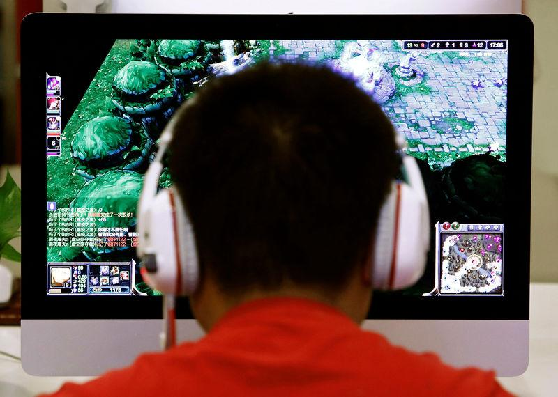 FILE PHOTO: A man plays a computer game at an internet cafe in Beijing