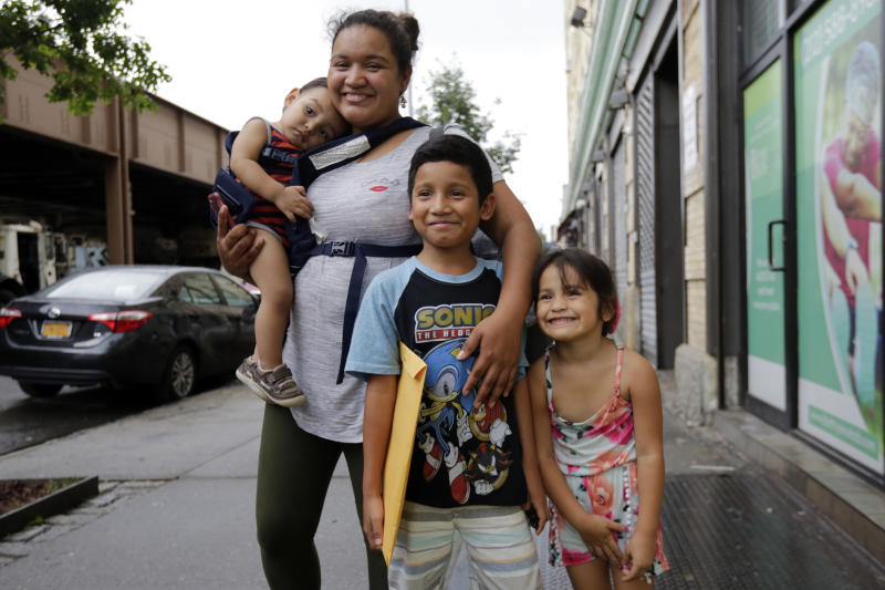 In this Friday, Aug. 3, 2018, photo, Nahun Eduardo Puerto Pineda, then 8, holding envelope, from Honduras, poses for a photo with his mother, Eilyn Carbajal, and two siblings after being reunited with them at the Cayuga Center, in New York. (AP Photo/Richard Drew)