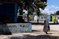 Woman walks past graffiti inside the Ritsona camp for refugees and migrants