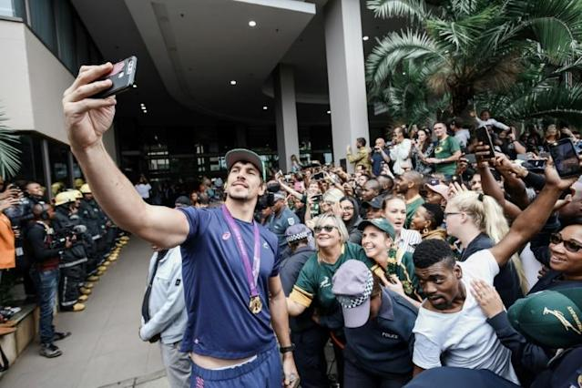 All smiles: Eben Etzebeth takes a selfie with supporters as the World Cup winners paraded in Durban earlier this month (AFP Photo/SBU NDLOVU)