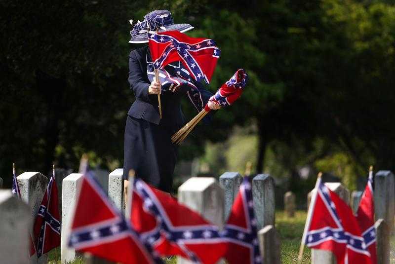 "FILE - A member of the United Daughters of the Confederacy collects Confederate flags after the Confederate Memorial Day ceremony at Magnolia Cemetery in Charleston, S.C. on Tuesday, May 10, 2011. Southern white men don't usually drive racial dialogue. For as long as race has riven America, they have been depicted more often as the problem than the solution. So the country music star Brad Paisley must have been unsurprised at the days of widespread criticism of his new song ""Accidental Racist,"" which details the challenges facing a ""white man from the southland"" and then features LL Cool J rapping from a black perspective. (AP Photo/The Post And Courier, Grace Beahm)"