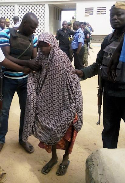 Zahra'u Babangida (C), a 14-year-old Nigerian girl arrested with explosives strapped to her body in Kano on December 10 following a double suicide bombing, is assisted to the Kano state police headquarters in Kano on December 24, 2014 (AFP Photo/Aminu Abubakar)