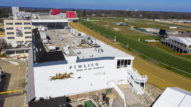 FILE - In this March 26, 2020, file photo, tractors groom the racing surface at the Pimlico Race Track in Baltimore, Md. The Preakness will remain at Pimlico Race Course into the foreseeable future, thanks to the passing of a bill to redevelop Maryland's race tracks with $375 million in bonds. (AP Photo/Steve Helber, File)