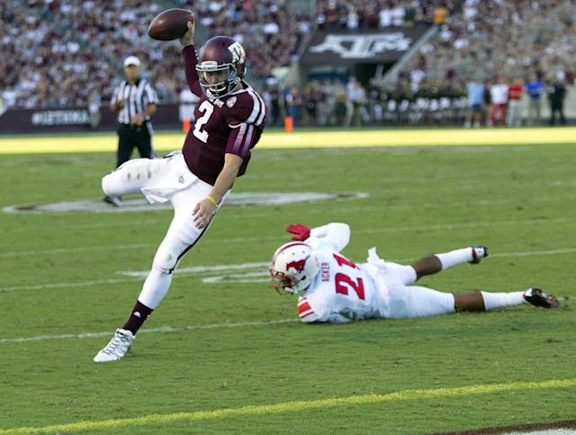 FILE - In this Sept. 14, 2013, file photo, Texas A&M quarterback Johnny Manziel (2) rushes for a 7 yard touchdown as he avoids the tackle of SMU defensive back Kenneth Acker (21) during the first quarter of an NCAA college football game in College Station, Texas. Manziel has put up eye-popping numbers similar to and in some cases better than he did a year ago, but most polls don't have him favored to join Archie Griffin as the second two-time Heisman winner. (AP Photo/Bob Levey, File)
