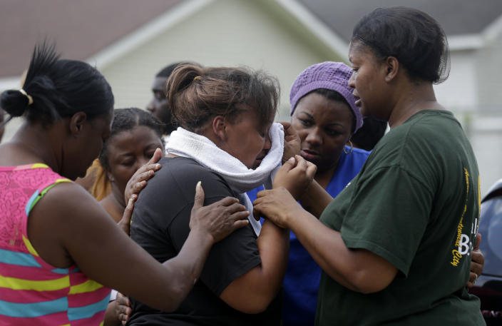 Lisa North, the mother of missing 6-year-old Ahlittia North, is comforted by her mother, Rene' Johnson, right, and others, after she says Jefferson Parish authorities have found the body of her daughter in a Harvey trash bin, in Harvey, La., Tuesday, July 16, 2013. Ahlittia disappeared from her apartment late Friday night or early Saturday morning. North's husband Albert Hill said they were told the body was found in a trash bin not far from their apartment. (AP Photo/Gerald Herbert)