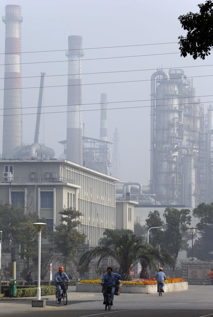 Workers pedal by the Sinopec Zhenhai petrochemical factory where an expansion was proposed on the outskirts of Ningbo city in eastern China's Zhejiang province Monday, Oct. 29, 2012. After three days of protests by thousands of citizens over pollution fears, a local Chinese government relented and agreed that the petrochemical factory would not be expanded, only to see the protests persist. (AP Photo/Ng Han Guan)