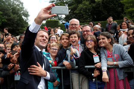French President Emmanuel Macron makes selfie with children during a ceremony marking the 78th anniversary of late French General Charles de Gaulle's resistance call of June 18, 1940, at the Mont Valerien memorial in Suresnes, near Paris, France, June 18, 2018.   REUTERS/Charles Platiau/Pool