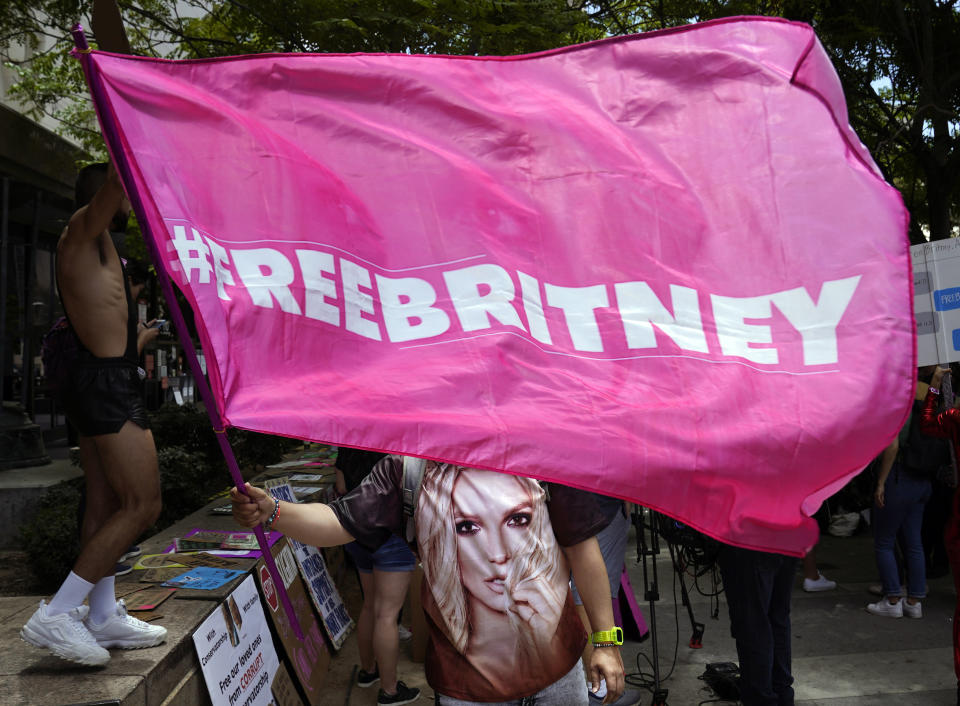 """A Britney Spears supporter waves a """"Free Britney"""" flag outside a court hearing concerning the pop singer's conservatorship at the Stanley Mosk Courthouse, Wednesday, June 23, 2021, in Los Angeles. (AP Photo/Chris Pizzello)"""
