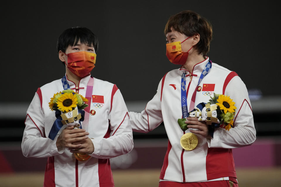 Shanju Bao, left, and Tianshi Zhong, of China, celebrate their gold medals during a ceremony for the track cycling women's team sprint finals at the 2020 Summer Olympics, Monday, Aug. 2, 2021, in Izu, Japan. (AP Photo/Christophe Ena)