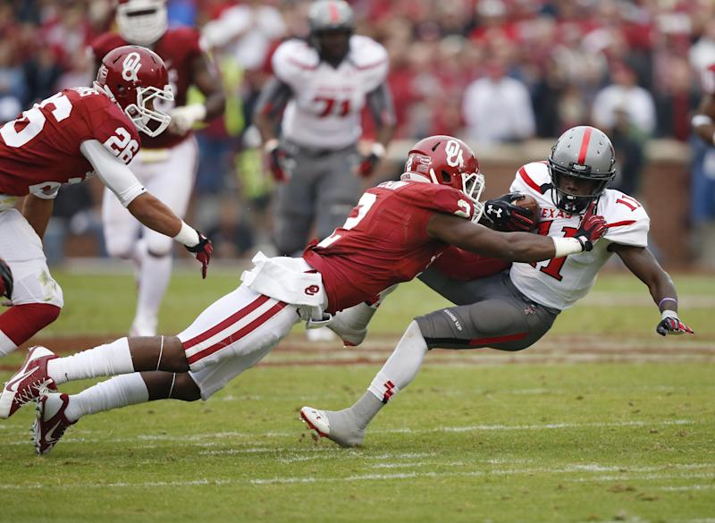Oklahoma defnsive back Julian Wilson (2) tackled Texas Tech wide receiver Jakeem Grant (11) in the first quarter of an NCAA college football game in Norman, Okla., Saturday, Oct. 26, 2013. (AP Photo/Sue Ogrocki)