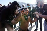 A counter demonstrator, center, yells after getting maced in the face by far-right demonstrators outside of City Hall Wednesday, Jan. 6, 2021, in Los Angeles. Demonstrators supporting President Donald Trump are gathering in various parts of Southern California as Congress debates to affirm President-elect Joe Biden's electoral college victory. (AP Photo/Marcio Jose Sanchez)