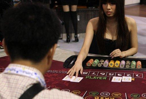 A hostess deals cards during a baccarat demonstration