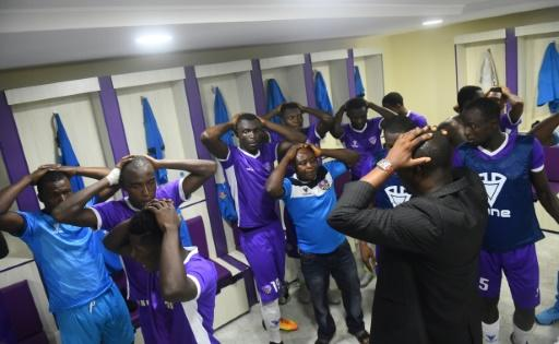Players and officials of Mountain of Fire and Miracles Ministries football club pray in the changing room before a game at Agege Stadium
