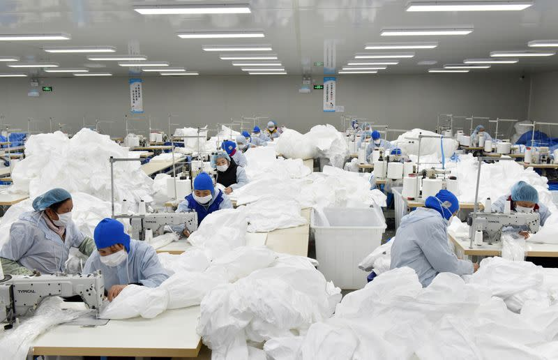 Workers make protective suits at a factory, as the country is hit by an epidemic of the new coronavirus, in Chaohu, Anhui