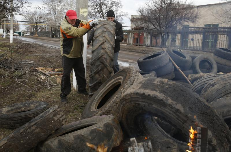 Pro Russian activists block a road with car tires near the armory Ukrainian army to prevent the export of arms and ammunition in the village of Poraskoveyevka, eastern Ukraine, Thursday, March 20, 2014. The disheveled men barricading the muddy lane leading into a military base in this eastern Ukraine village say they're taking a stand to defend Russian-speakers. (AP Photo/Sergei Grits)