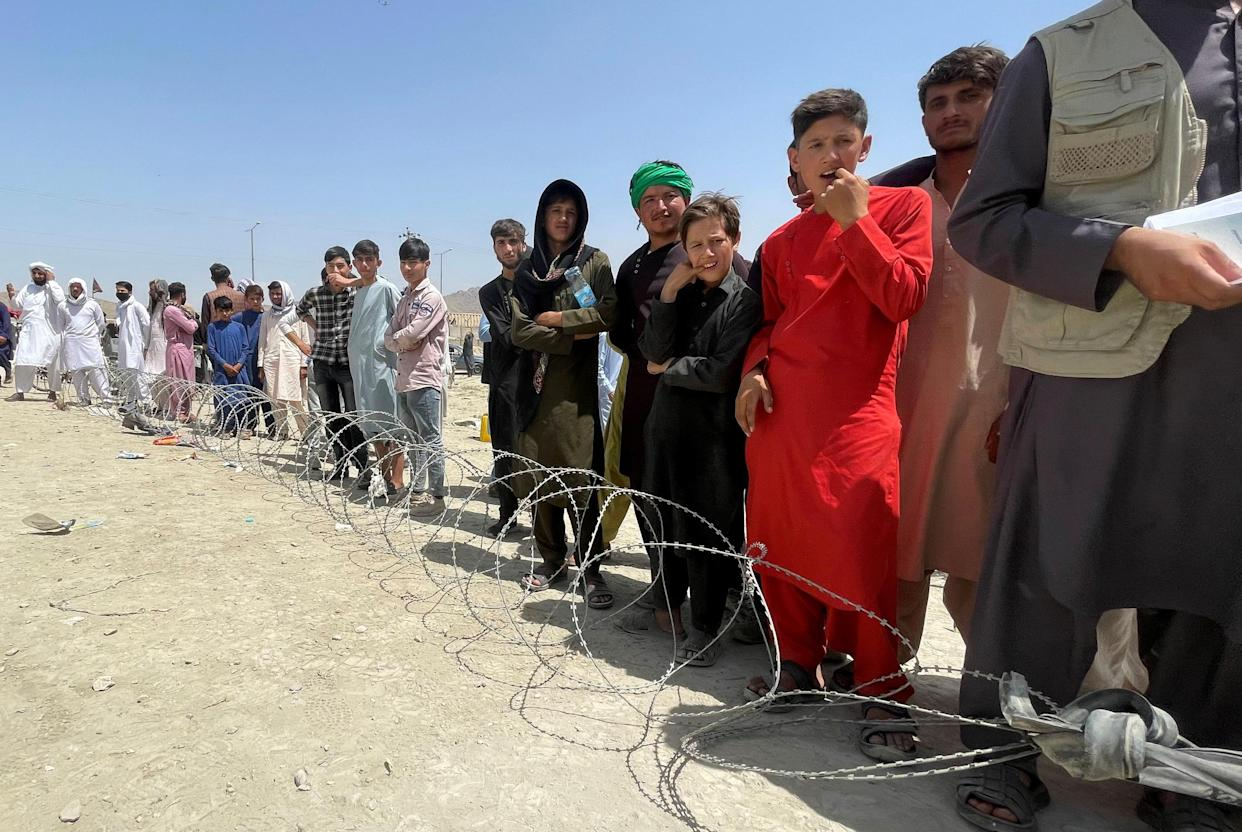 People wait outside Hamid Karzai International Airport in Kabul on Tuesday.