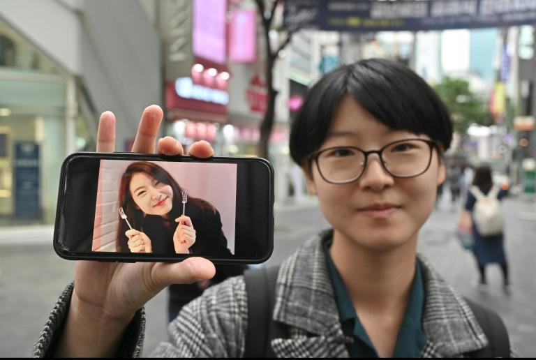 South Korean woman Yoon Ji-hye displaying an old photo of herself, before she embraced a feminist movement that shuns traditional patriarchal expectations (AFP Photo/Jung Yeon-je)