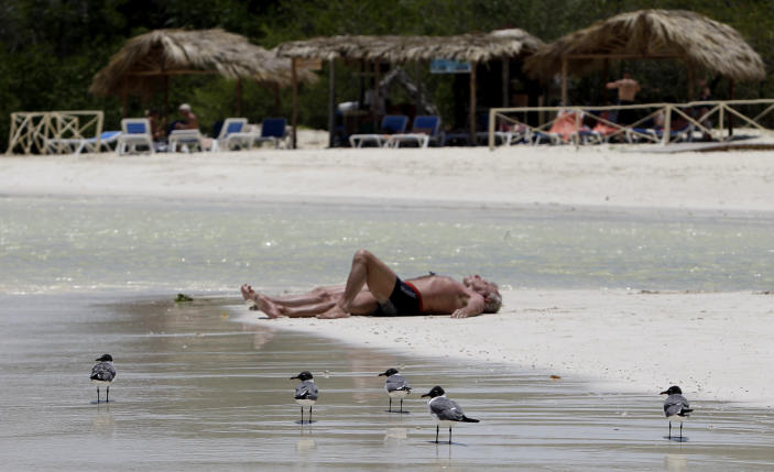 In this May 20, 2013 photo, sea gulls walk along the beach where tourists sunbathe in Cayo Coco, in Ciego de Avila, Cuba. Cuba has had a coastal protection law on the books since 2000 that prohibits construction on top of sand and mandates a buffer zone from dunes, but serious enforcement only began in earnest in recent months. (AP Photo/Franklin Reyes)
