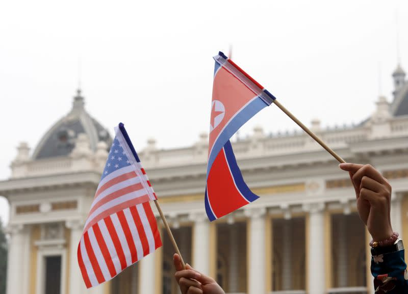 Residents hold US and North Korean flags while they wait for motorcade of North Korea's leader Kim Jong Un en route to the Metropole Hotel for the second US- North Korea summit in Hanoi