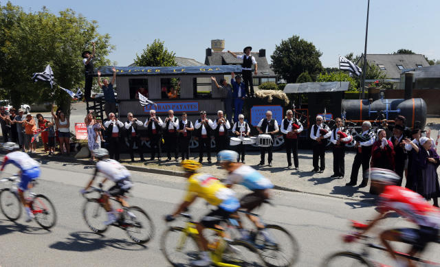 Musicians perform on the side of the road as the pack with Belgium's Greg van Avermaet, wearing the overall leader's yellow jersey, centre, rides during the sixth stage of the Tour de France cycling race over 181 kilometers (112.5 miles) with start in Brest and finish in Mur-de-Bretagne Guerledan, France, Thursday, July 12, 2018. (AP Photo/Peter Dejong)