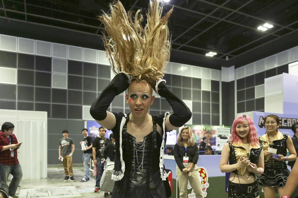 <p>A performer from IDEA Entertainment putting on his wig after a sing-along session at the Asia Game Festival 2018. (PHOTO: Don Wong) </p>