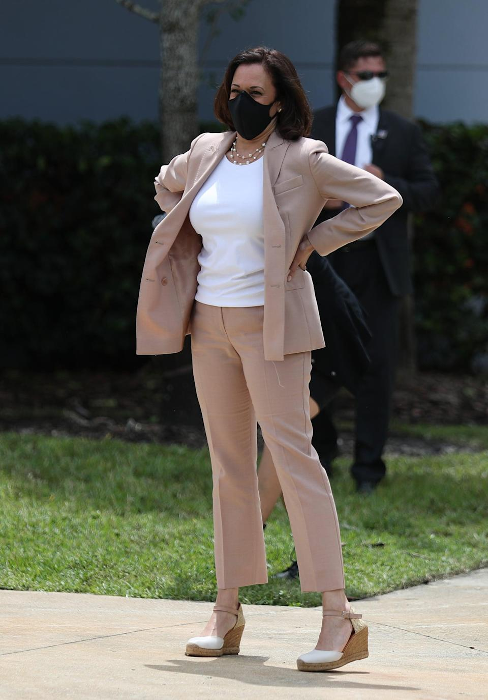 <p>Kamala's September 2020 Miami campaign stop called for a fitted camel suit, the blazer worn undone, with her chainlink pearls, espadrille wedges, and a protective face mask.</p>