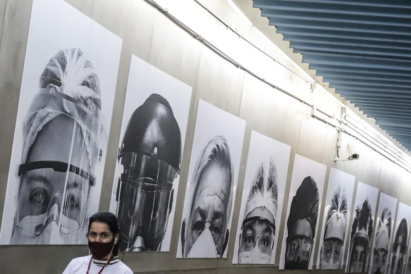SAO PAULO, July 22, 2020 -- A woman walks past a collection of medical workers' pictures at a subway station in Sao Paulo, Brazil, July 21, 2020. Brazil on Tuesday reported a total of 2,159,654 people have tested positive for COVID-19 and 81,487 patients have died from the disease. Brazil is one of the countries hardest hit by the pandemic, second only to the United States, both in terms of death toll and caseload. (Photo by Rahel Patrasso/Xinhua via Getty) (Xinhua/ via Getty Images)