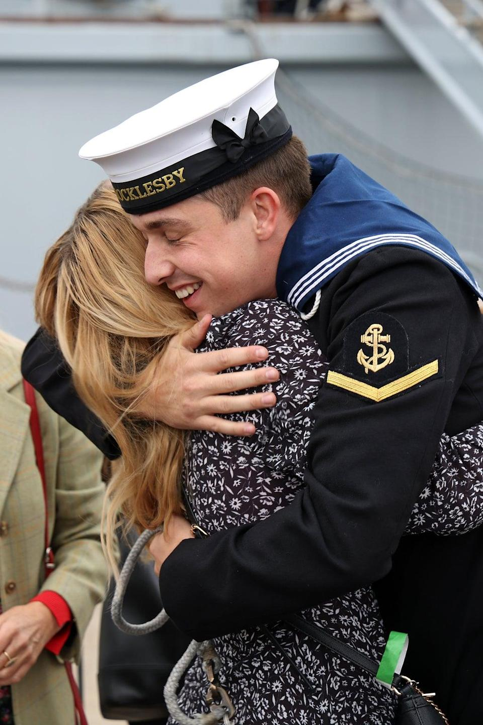 A sailor from HMS Brocklesby is welcomed home by a loved one at Portsmouth Naval Base (Royal Navy/PA)