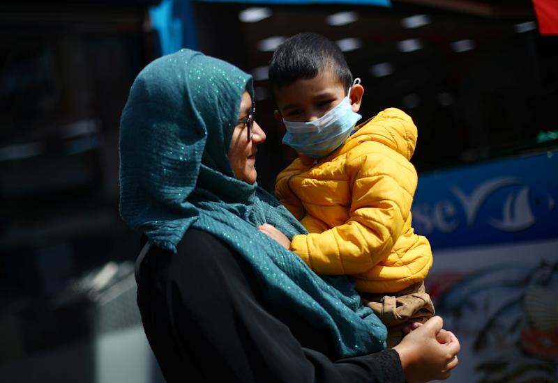 A woman carries a child in her arms who wears a face mask in Tooting, following the outbreak of the coronavirus disease (COVID-19), London, Britain, May 4, 2020. REUTERS/Hannah McKay