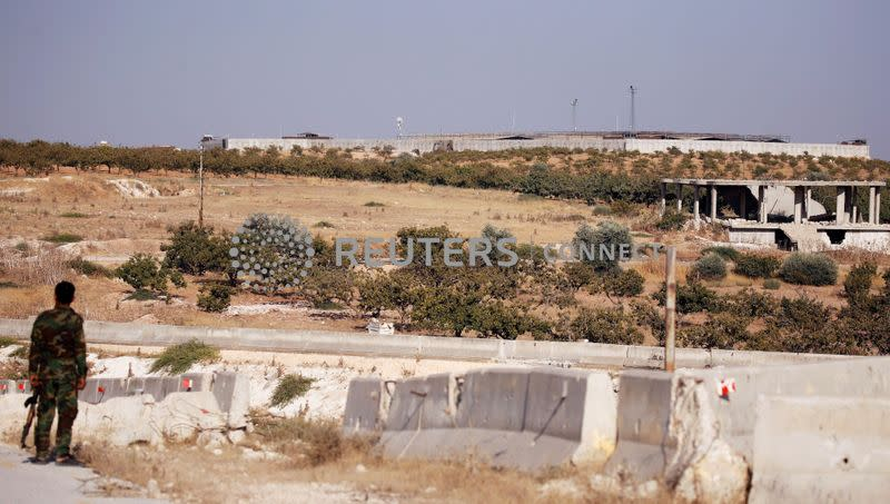 FILE PHOTO: A Syrian army soldier stands near the Turkish observation point in the town of Morek, Hama province
