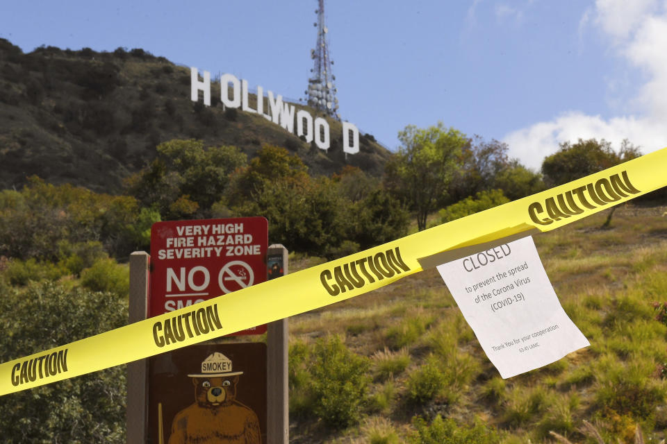 FILE - In this March 28, 2020, file photo, a sign is posted at the closed entrance to Innsdale Trail near the Hollywood sign in Los Angeles, amid the coronavirus pandemic. Now, in early May 2021, California has the lowest case rate in the country. (AP Photo/Mark J. Terrill, File)