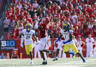 Rutgers wide receiver Bo Melton (18) catches a pass for a 57-yard gain as Delaware defensive back Justis Henley (21) and defensive back Kedrick Whitehead (1) defend during the first half of an NCAA college football game Saturday, Sept. 18, 2021, in Piscataway, N.J. (Andrew Mills/NJ Advance Media via AP)