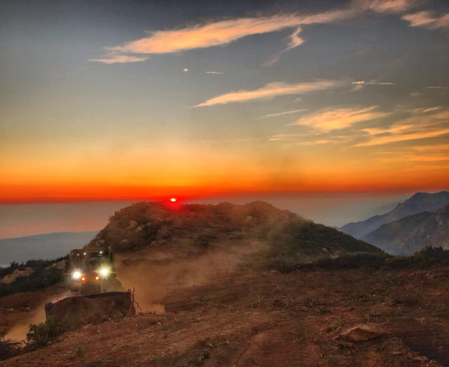 <p>A dozer from the Santa Barbara County Fire Department clears a fire break across a canyon from atop Camino Cielo down to Gibraltar to make a stand should the fire move in that direction, Wednesday, Dec. 13, 2017, in the Santa Ynez Mountains area of Santa Barbara, Calif. (Photo: Mike Eliason/Santa Barbara County Fire Department via AP) </p>