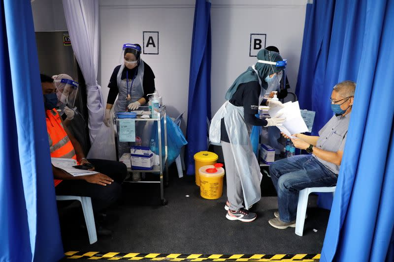 Construction workers receive doses of the Sinovac vaccine against the COVID-19, in Kuala Lumpur