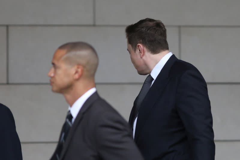 Elon Musk walks with his face turned away from cameras as he arrives at court for trial in Los Angeles