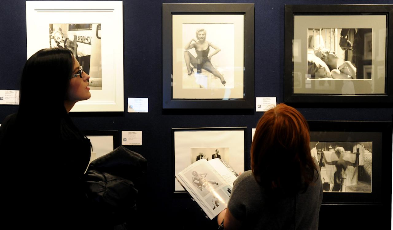 Potential bidders look at Marylin Monroe photos prior to an auction of pictures by the late celebrity photographer Milton H. Greene, in Warsaw, Poland, Thursday, Nov. 8, 2012. (AP Photo/Alik Keplicz)