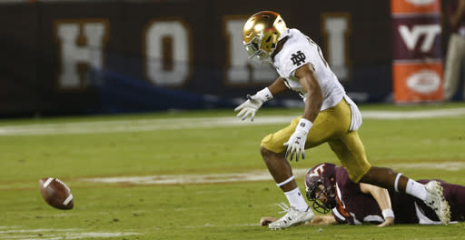 Notre Dame cornerback Julian Love (27) heads for the fumble as Virginia Tech quarterback Ryan Willis (5) watches during the first half of an NCAA college football game in Blacksburg, Va., Saturday, Oct. 6, 2018. Love recovered the ball and ran for a touchdown. (AP Photo/Steve Helber)
