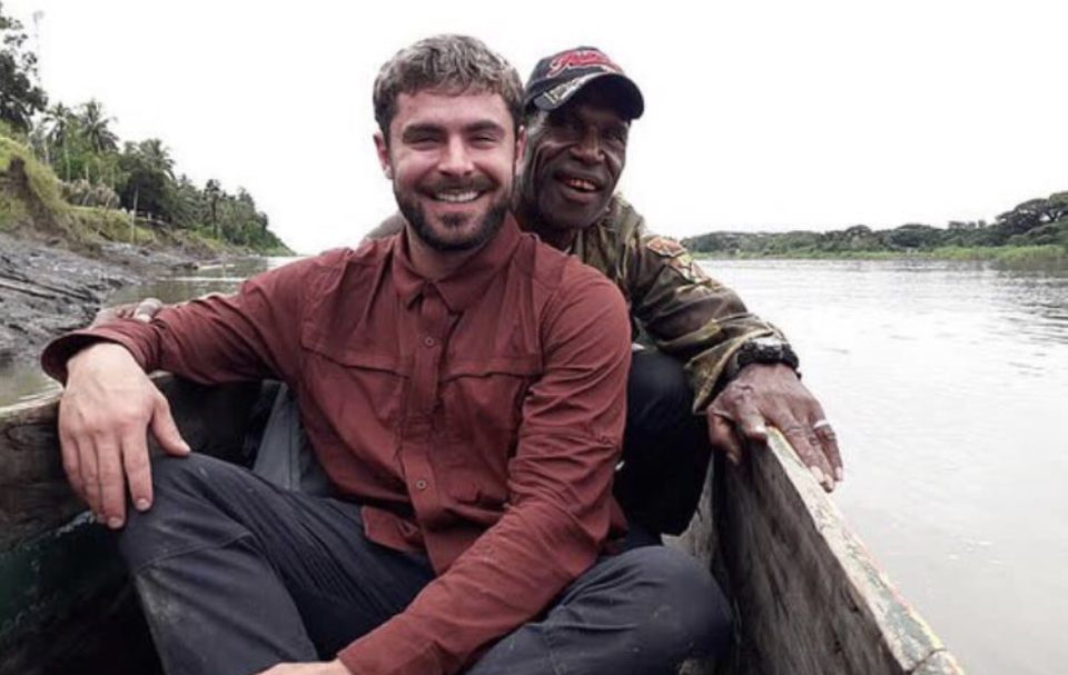 Zac Efron sits in a canoe while filming Killing Zac Efron in Papua New Guinea