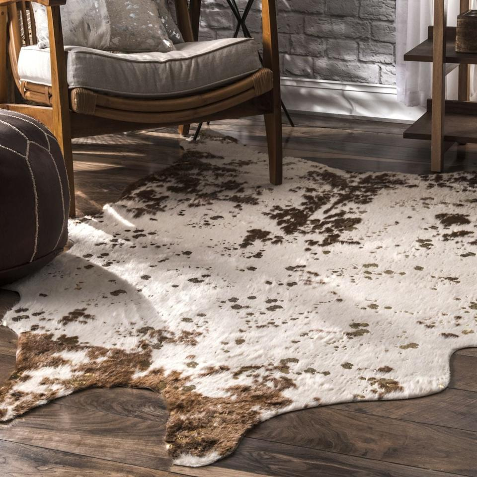 """<p>To be honest, I didn't exactly notice that the<product href=""""https://www.rugsusa.com/rugsusa/rugs/rugs-usa-macchiato-faux-cowhide/Brown/200BIBR01C-5067.html"""" target=""""_blank"""" class=""""ga-track"""" data-ga-category=""""Related"""" data-ga-label=""""https://www.rugsusa.com/rugsusa/rugs/rugs-usa-macchiato-faux-cowhide/Brown/200BIBR01C-5067.html"""" data-ga-action=""""In-Line Links"""">Vaquero Macchiato Faux Cowhide Rug </product> ($109) came with gold-fleck accents when I hit the """"order"""" button, but I've come to love the added detail. My main concern was that they would peel off the second I vacuumed, but they've held strong for five months and counting.</p>"""